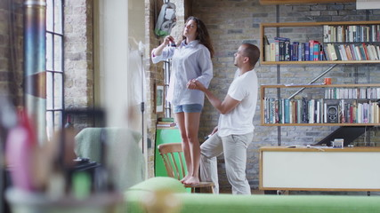 Romantic young couple painting their apartment