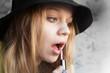 Portrait of blond teenage girl in black hat doing make up