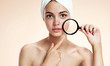girl with problem skin look at pimple with magnifying glas - 80570693