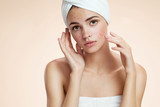 Scowling girl show her acne with towel on her head poster
