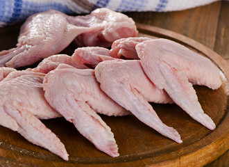 Uncooked  chicken wings on a  wooden board