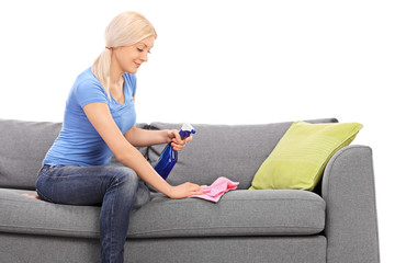 Blond woman cleaning a sofa with a rag