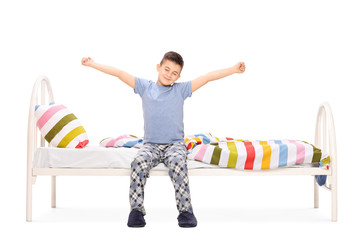 Little boy stretching seated on a bed