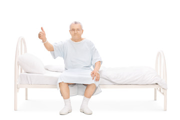 Mature patient sitting on a bed and giving thumb up