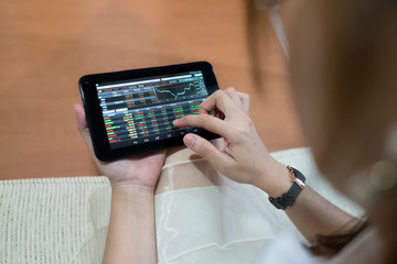 Woman using tablet to check the stock market