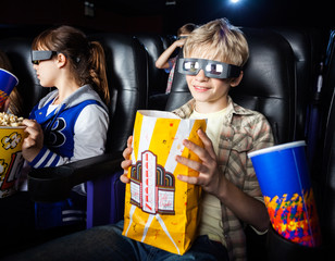 Boy Having Snacks While Watching 3D Movie With Sister