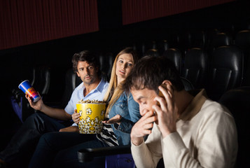 Angry Couple Looking At Man Using Mobilephone In Theater