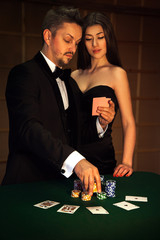 Nice man in elegant suit looking cards with his sexual woman and