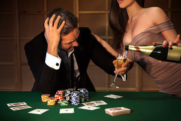 Photo emotional man loser in poker and ladies pours him a glass