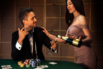beauty guy flirting with a girl who pours champagne at the poker