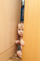 Curious cute baby boy looking through ajar door