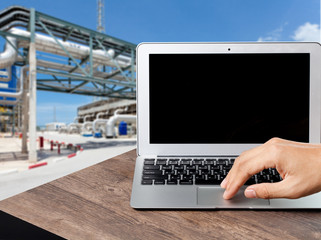 Engineer using a laptop at factory, plant background