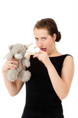 attractive smiling brunette holding teddy bear grimacing with pe