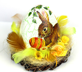 Rabbit, sit and holding colorful eggs in basket
