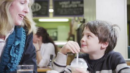 Cute little boy in a cafe enjoys sharing his milkshake