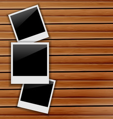 Three blank photo frames on wooden background