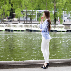 Full length portrait of a beautiful woman in white pants and blu