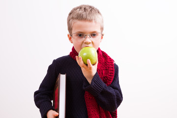 Young boy with a book and apple