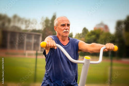 Senior man work out in outdoor fitness gym - 80576404