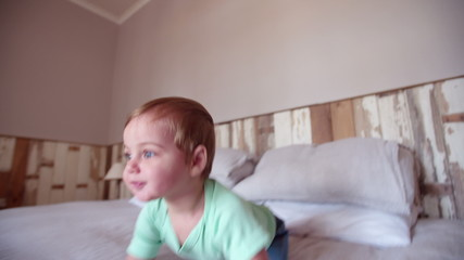 Baby boy adventurer crawling and exploring the bed