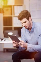 mann am schreibtisch schaut auf tablet-pc