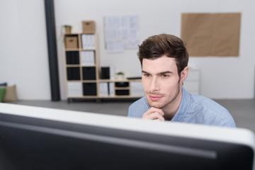 mann im büro schaut konzentriert auf seinen bildschirm