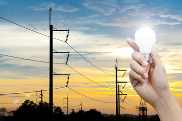 Hand holding a glowing light bulb and electricity pole sunset ba