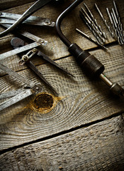 Old drill, compasses, ruler and drills on a wooden background.