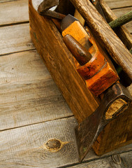 Old working tools  in box on wooden background.