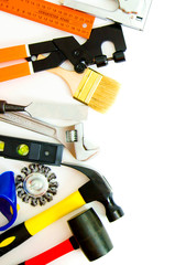 Many working tools - hammer, ruler, spanner and others on white