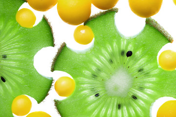 Close up of kiwi slices and vitamin pills isolated on white, hea