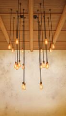 ceiling light bulb hanging on pine wood against warm tone of gru