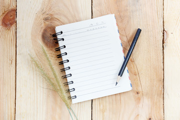Note book and pencil on wooden background
