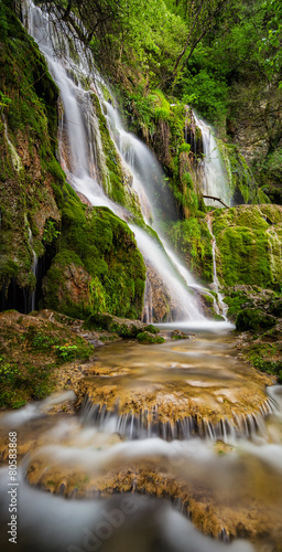 Tuinposter Watervallen Beautiful waterfall among cliffs in spring time