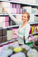 woman with shopping basket choosing flowerpot