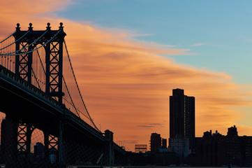 Manhattan Bridge and skyline silhouette at sunset