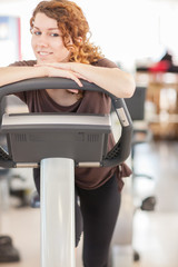 Smiling caucasian woman doing exercise on a fitness bike