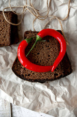 Pieces of dark rye bread with chili pepper on a crumpled paper.T