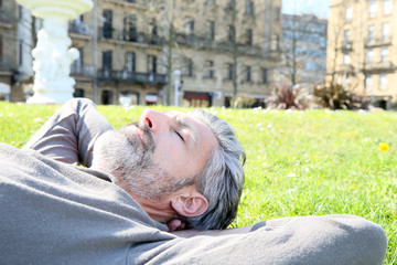 Mature man having a nap in city park