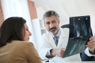 Surgeon showing X-ray to patient in medical office