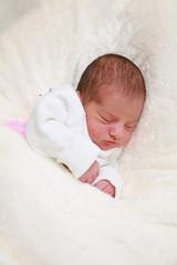Neugeborenes Mädchen schläft und träumt ruhig und zufrieden