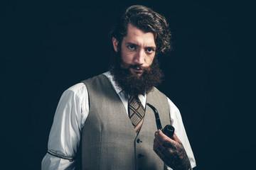 Stylish man with a beard smoking a pipe