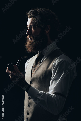Elegant Young Handsome Guy Holding a Smoking Pipe