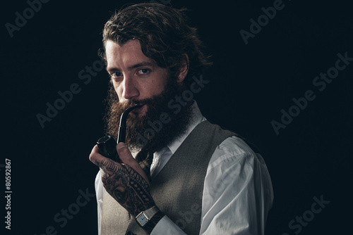 Handsome Young Man Smoking Using a Tobacco Pipe