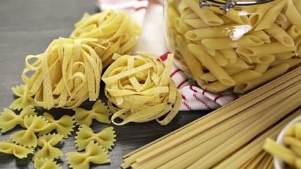 Variety og organic dry pasta on wood board.