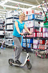 Woman trying scooter in sports shop