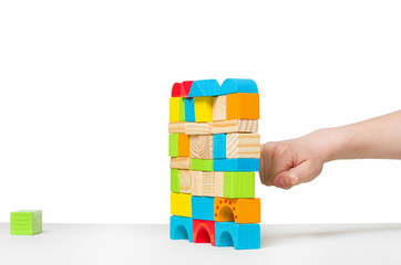 fist destroying house made of color wooden blocks