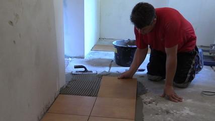 Handyman worker place floor tiles. Home improvement, renovation