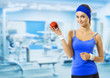 Woman in sportswear with red apple, at gym