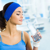 Woman drinking water at gym